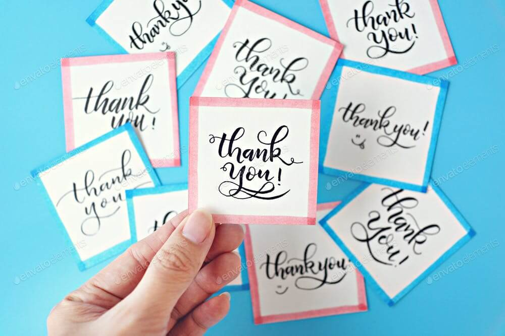 Hand holding Thank You card on blue background. (1)
