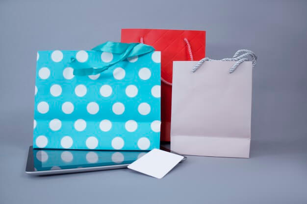 Online shopping concept. close-up tablet mockup with white screen and credit card against the wall of bright gift bags. Premium Photo
