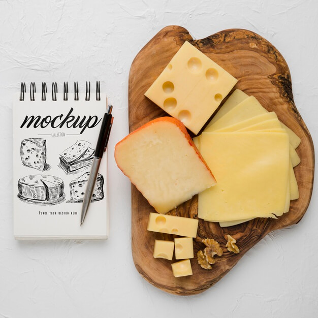 Top view of notebook with pen and variety of cheese Free Psd