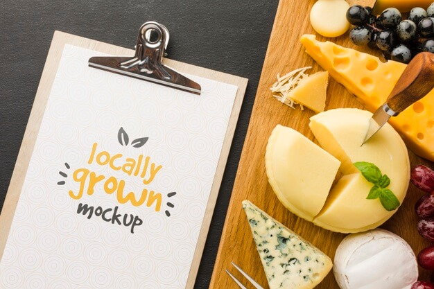 Top view of notepad with assortment of locally grown cheese mock-up Free Psd