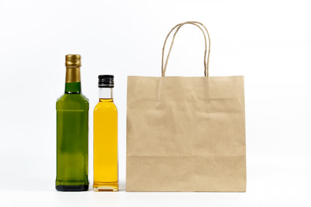 Yellow and green glass bottle with paper bag isolated on a white background. Premium Photo