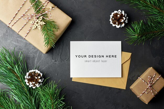 Greeting card mockup with christmas gift boxes and pine branches and cones Premium Psd