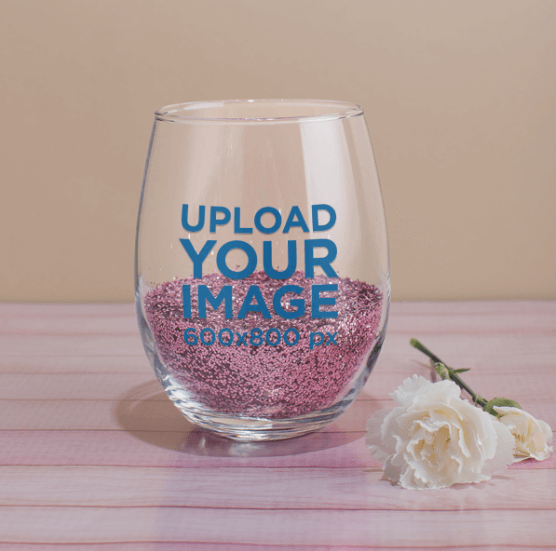 Stemless Wine Glass Mockup Featuring Pink Glitter and a White Carnation